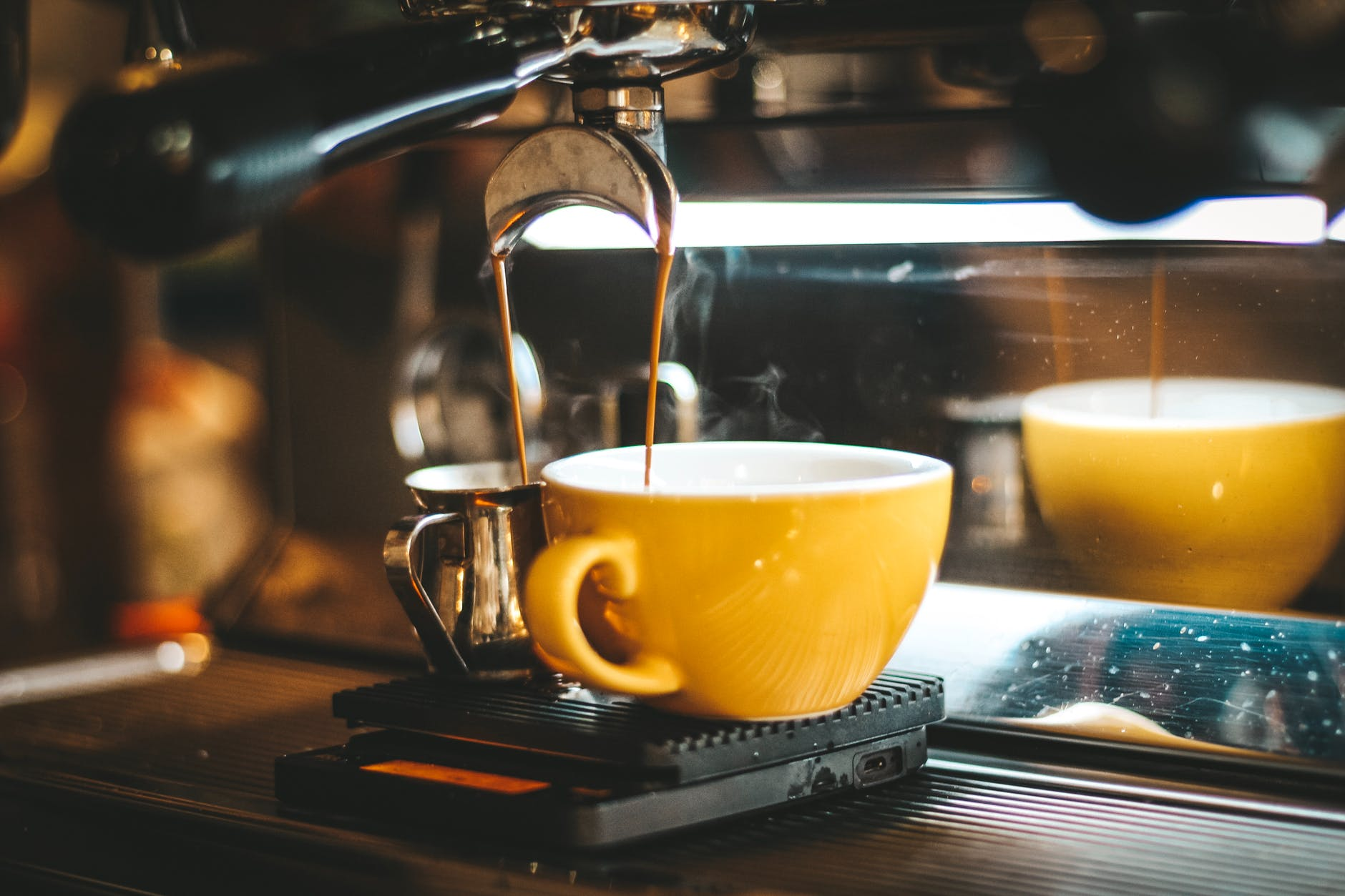 espresso machine dispensing on two mugs