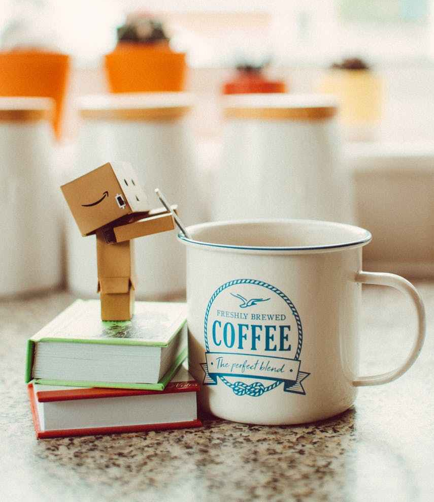 cartoon robot standing on books beside mug